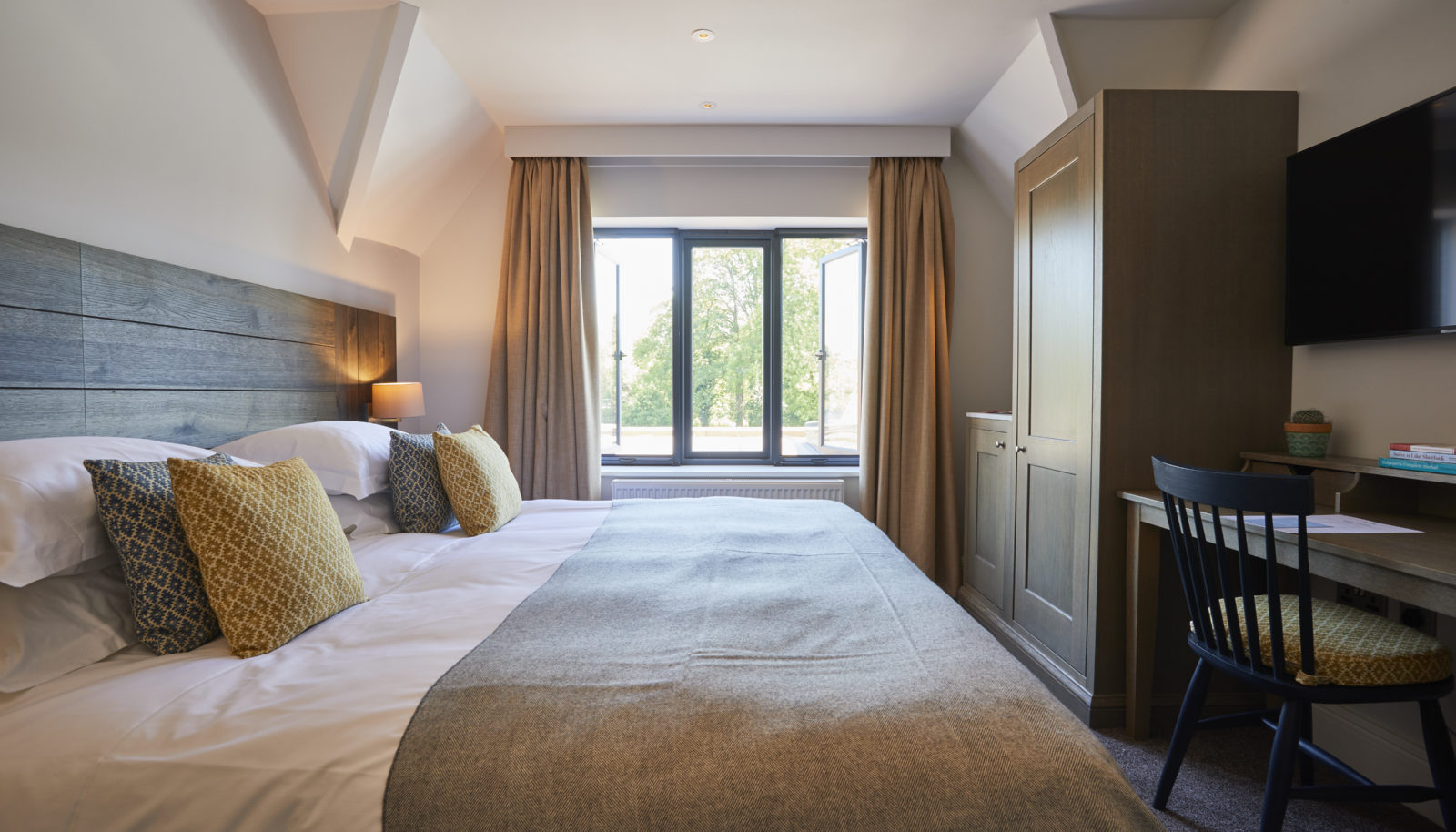 Medium double river view room with bed at riverside Hotel the Swan at Streatley