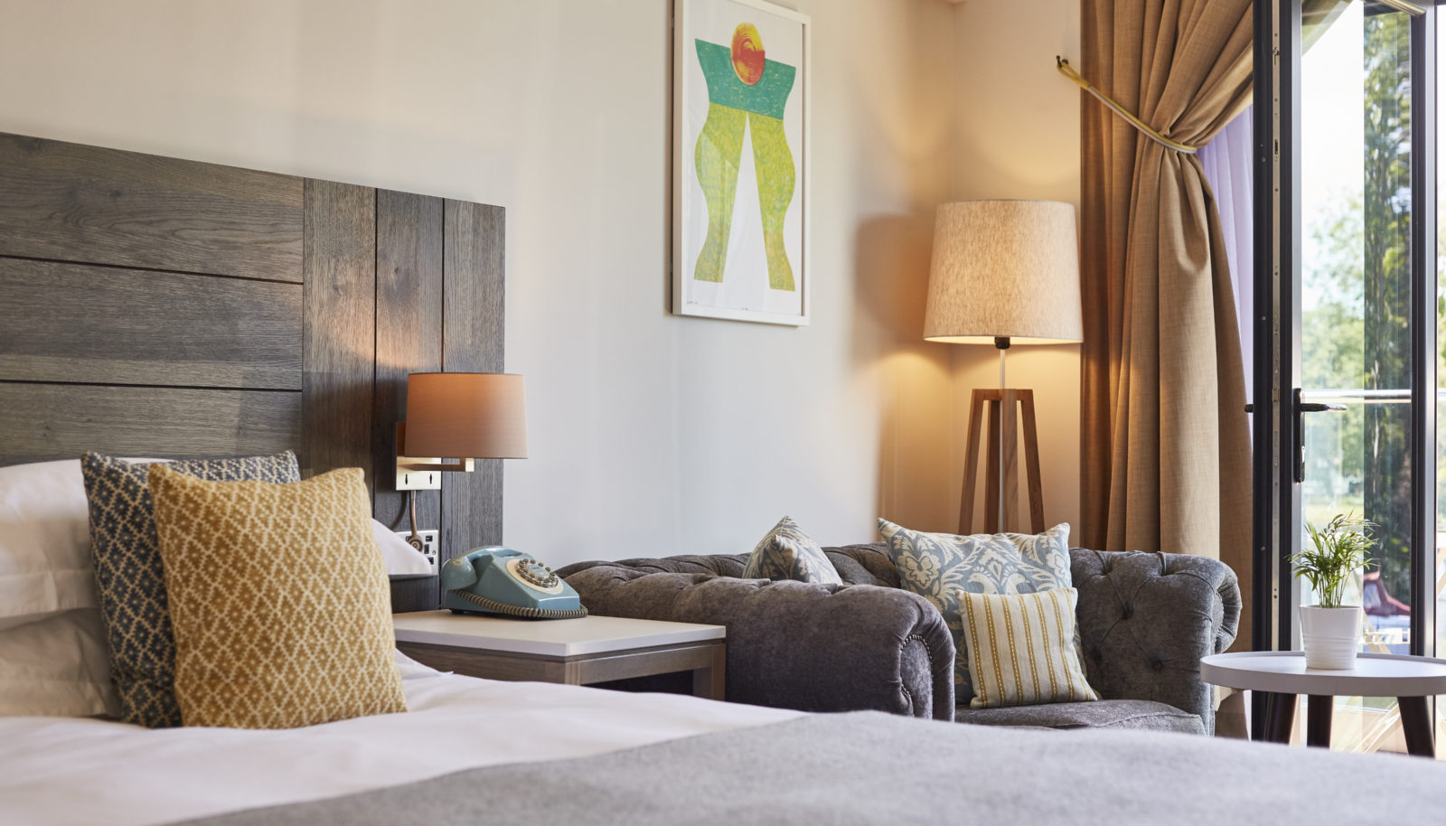 Large double hotel room with river view with cosy sofa and art at The Swan at Streatley