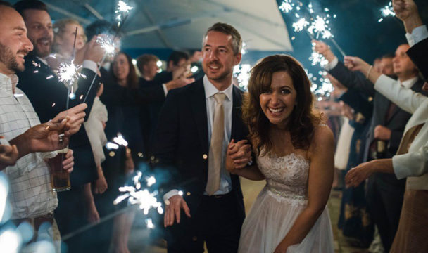 bride and groom in the evening with sparklers cheered by wedding guests